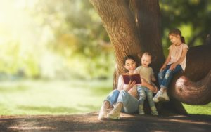 Goodwin Insurance Homepage - Mom Reading with Children Under a Tree